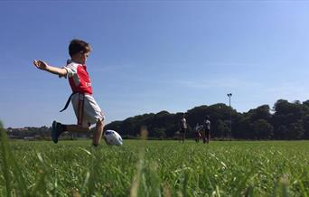 Child kicking a rugby ball