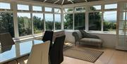 Conservatory showing table, chairs and sofa