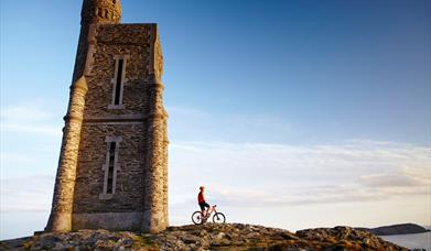 Cyclist taking in the views at Milner's Tower, Port Erin